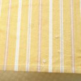 黄色いストライプのテーブルクロスの端にレース糸で刺しゅうがほどこされている