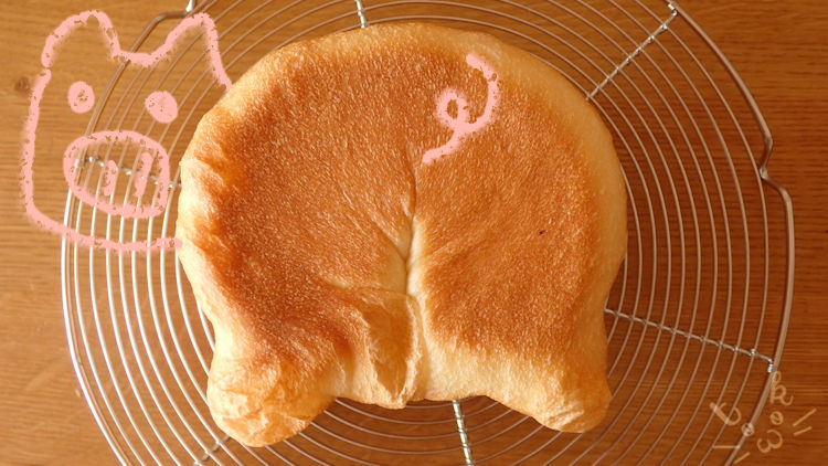 焼きあがったパンにブタのイラストを描き添えている