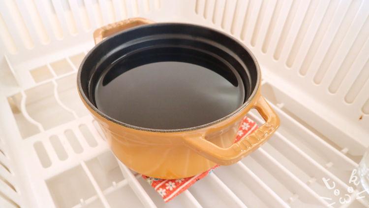 水切りかごのなかにお湯を張ったストウブの14cmサイズのココットが置かれている