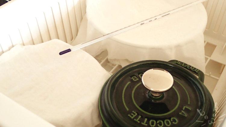 発酵器として使っている水切りかごの中に熱湯入りストウブとパン生地の入ったボウルと温度計を入れている