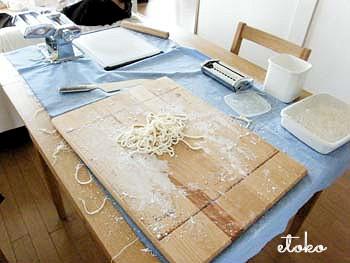 テーブルの上にパスタメーカー、綿棒、琺瑯容器などうどん打ちの道具が散乱している