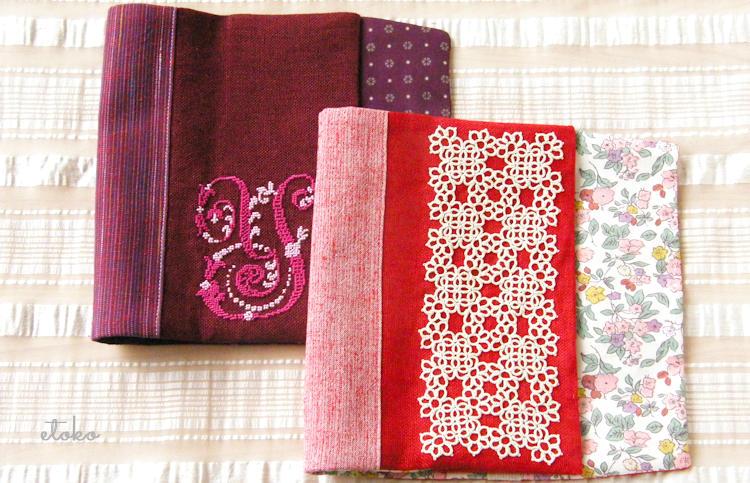 赤いリネンにエクリュの糸で編んだタティングレースを縫い付けたブックカバーとブドウ色のリネンにYのモノグラムステッチを刺した和風仕立てのブックカバー