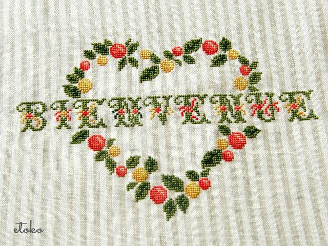 ベージュストライプのリネンにビタミンカラーのクロスステッチでフランス語の「ようこそ」と刺繍がしてある