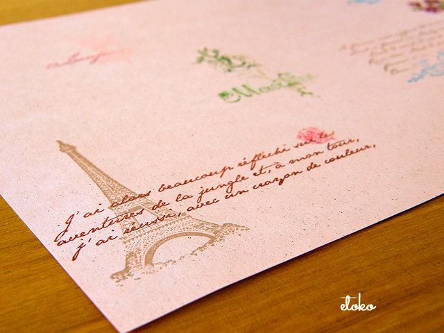 ピンク色の紙にエッフェル塔やフランス語の文字のスタンプが押されている