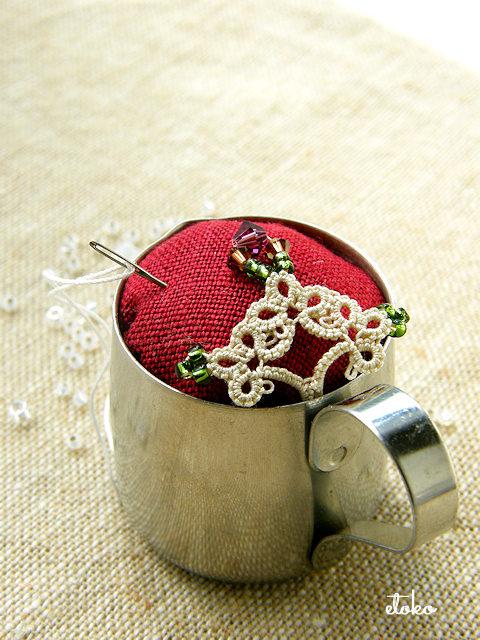 タティングレースにアンティーク風の配色のビーズを編み込んで、赤いリネンと合わせてミルクピッチャータイプのピンクッションを作っている