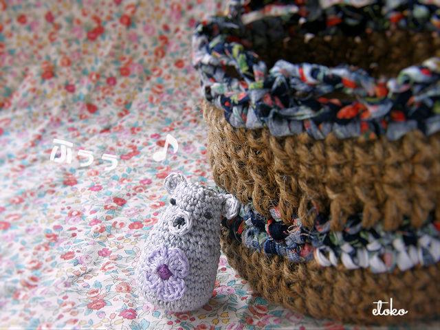 かぎ針編みの編みぐるみクマが麻糸のカゴに寄りかかっている