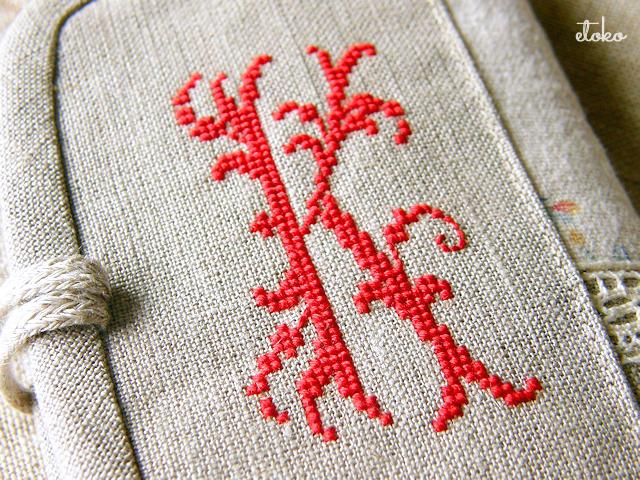 リネンに赤い刺繍糸でKのモノグラムステッチが施されている