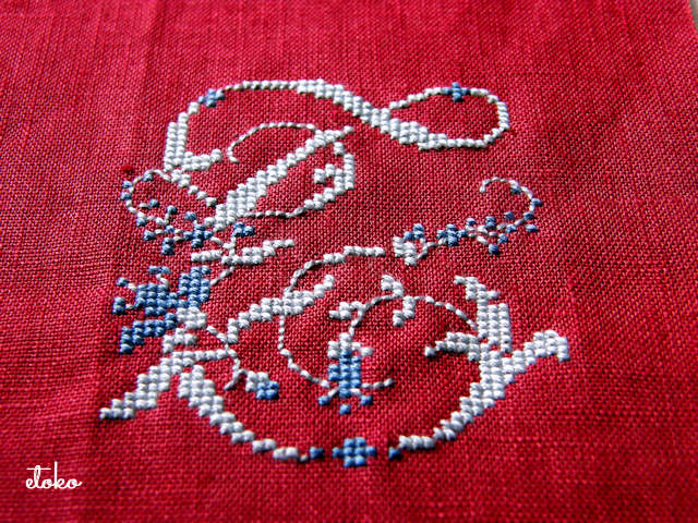 落ち着いた赤のリネンにブルーの糸でモノグラムステッチ