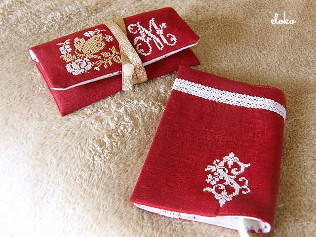 バラとモノグラムのクロスステッチで装飾された渋めの赤いリネンの眼鏡ケースとブックカバーが置かれています