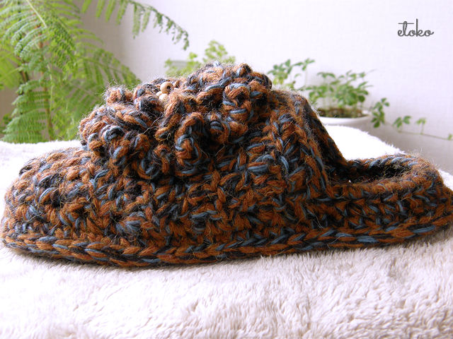 茶色と青色の太目の糸で編まれたスリッポンお花の飾りがついている