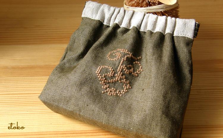 カーキ色のリネンに麻色の糸でいイニシャルFをクロスステッチ。