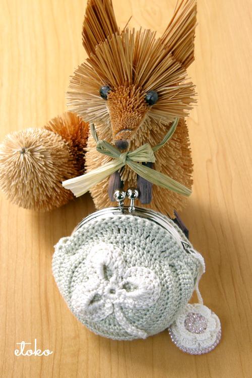 シャムロックのモチーフを縫い付けたかぎ針編みのがま口