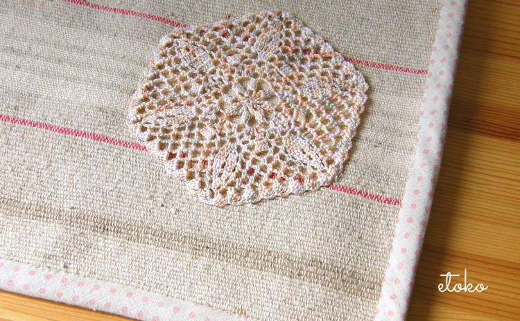 麻のバスマットにミックスレース糸で編んだクロッシェレースのドイリーを縫いつけてある