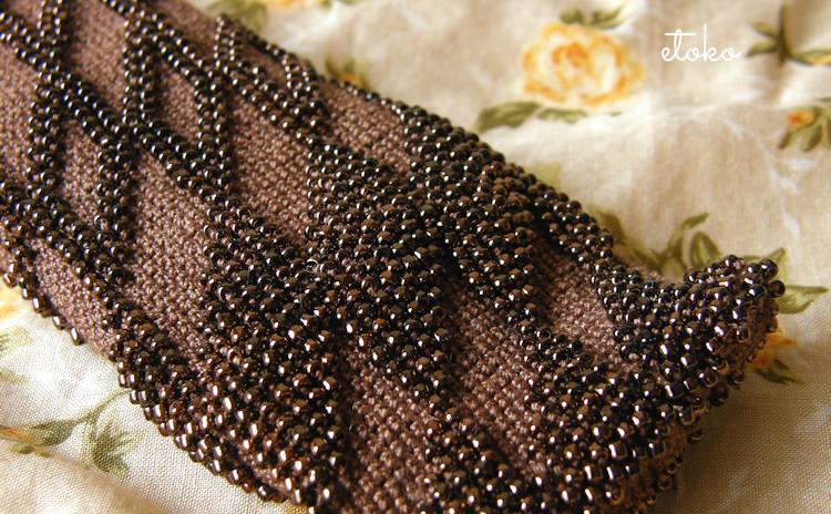 ブロンズカラーのビーズを編み込んだかぎ針編みの眼鏡ケース