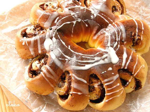チョコナッツを巻き込んだパンを花形に焼き上げ、トップに真っ白なアイシングをまぶしてある