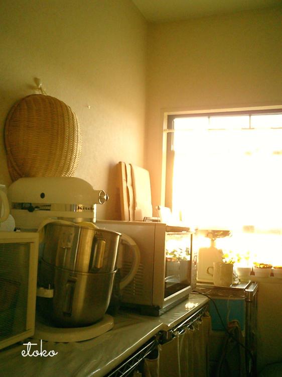 台所の棚にキッチンエイド、小さめの棚、キッチンスケール、オーブン、ペストリーボードが置かれ、壁には竹で編まれたざるがかけられている