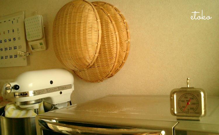 オーブンの上に温度計、その横にキッチンエイド、背面の壁にざると温度計とカレンダーがかけられている