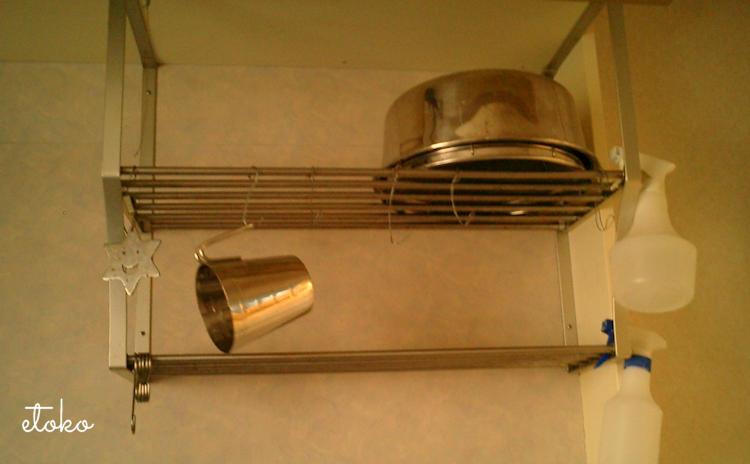 台所のシンク上の棚にたらいとざる計量カップにスプレーボトルが掛けてある