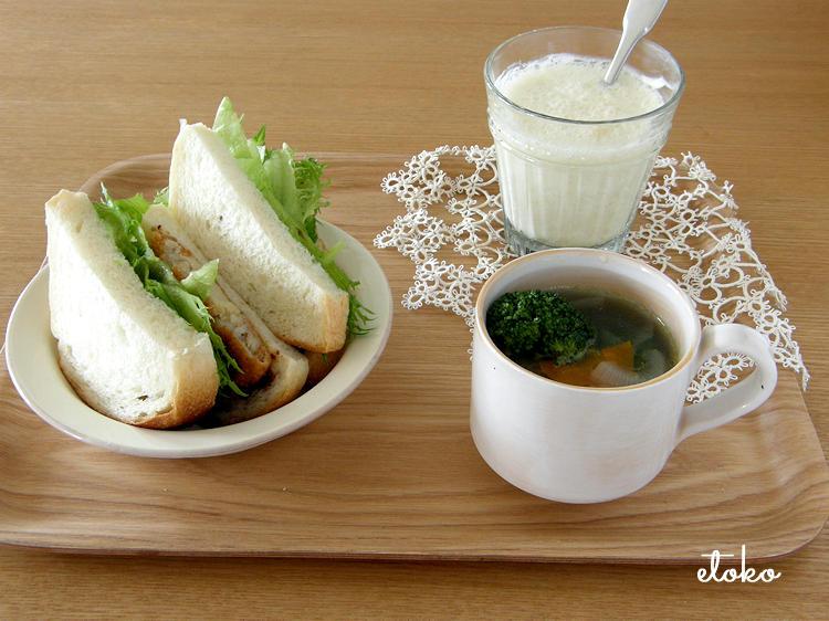 タティングレースを添えたトレイの上にコロッケパンサンドと野菜のスープ、ヨーグルトのジュースがのせられている