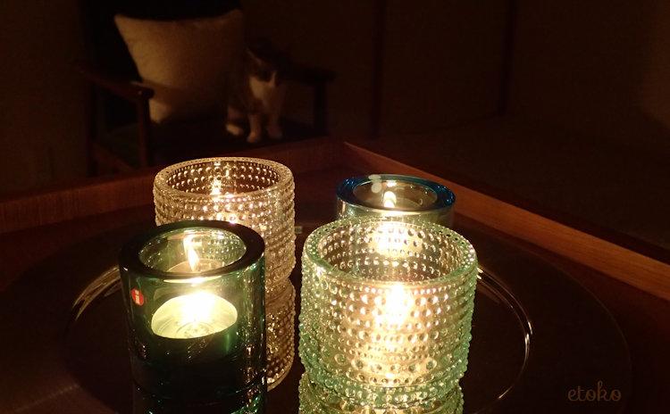 暗闇でkiviとカステヘルミのキャンドルホルダーを見つめる猫