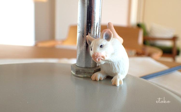 デスクライトの台座の上にネズミのフィギュアが置かれている