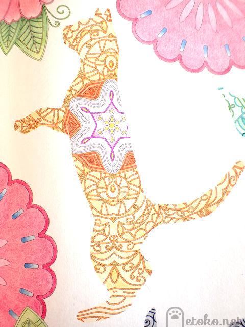『ねこと花もようの塗り絵ブック』よりオレンジ色のペンとシャーベットオレンジ色の色鉛筆で塗った猫の塗り絵