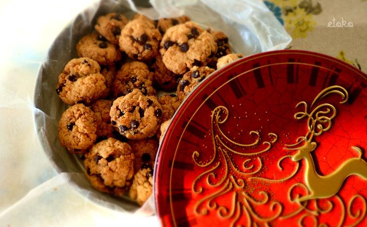 赤いクリスマスデザインの丸缶にココナッツファインを混ぜたチョコチップクッキーを入れている