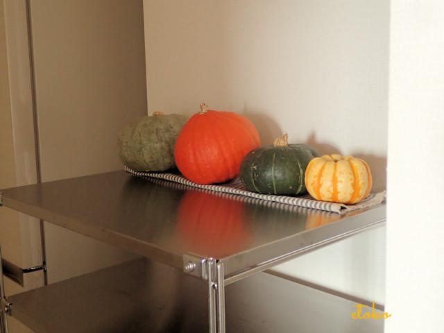 台所のシェルフの上に色とりどりのカボチャを飾っている