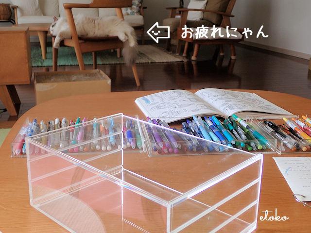 遠くにある椅子の上でぐったりのびているラグドールと散らばったゲルボールペンと塗り絵本