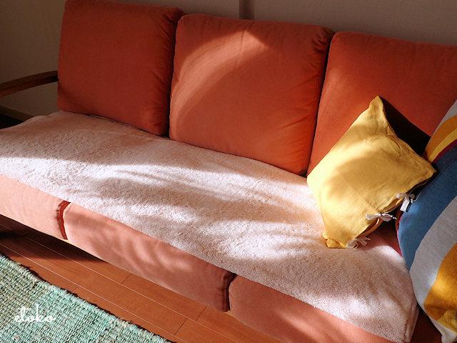 ソファの上に淡いピンクのブランケットを敷いている