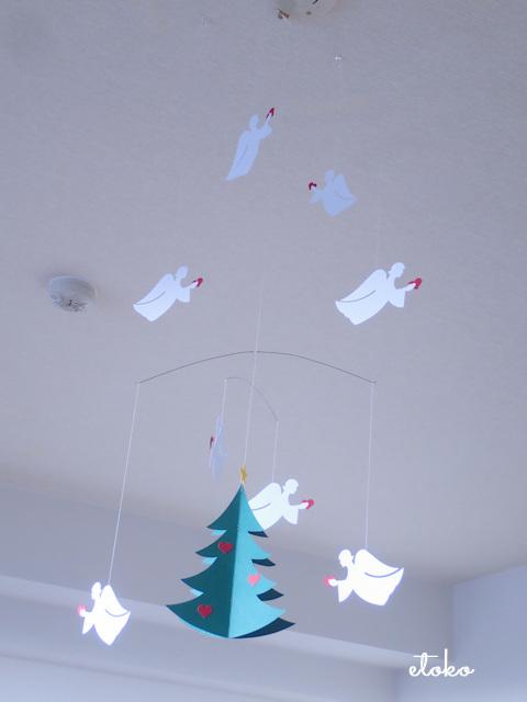 天井から紙製天使8体とツリーのモビールが吊り下げられている