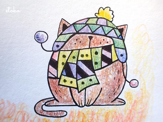 毛糸の帽子をかぶり、マフラーを巻いた茶色の猫が前足を揃えて座っている塗り絵