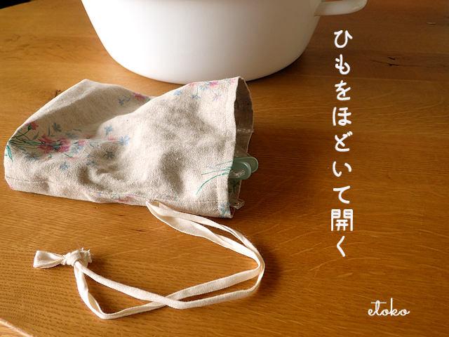洗濯バサミの入った巾着袋の口を開いてテーブルに置いている