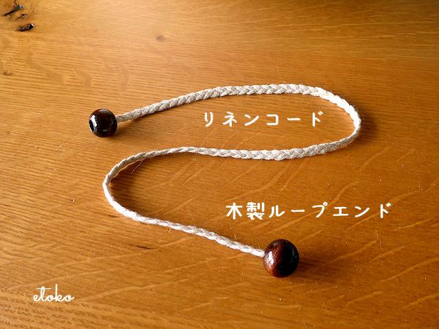 太目のリネンのコードの先端に木製ループエンドを通して端を結んで留めている