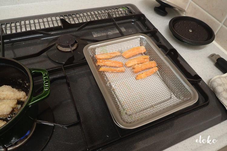 無印良品のステンレスメッシュトレーにかたくり粉をまぶして揚げたにんじんが置いてある。その隣のストウブの鍋では鶏の手羽中を揚げている
