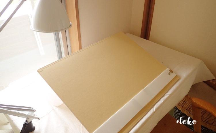 作業テーブルに置いた積み重ねボックスに立てかけて画板をおいている
