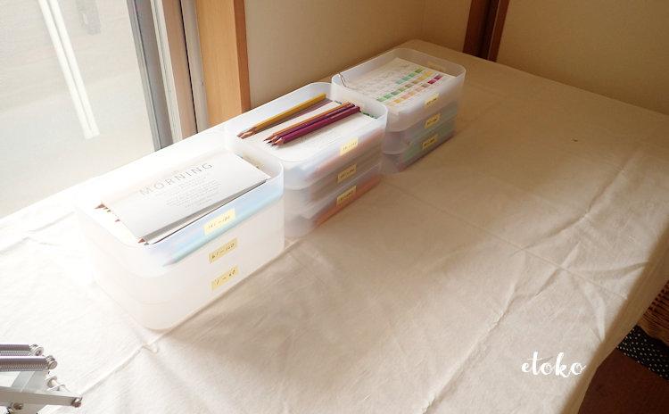作業テーブルにフェリシモの500色の色えんぴつを収納した積み重ねボックスを3段ずつ3つに分けておいている