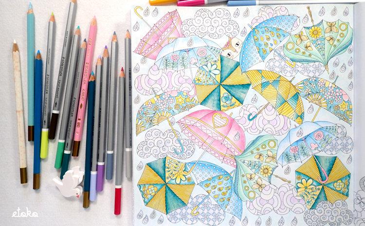 傘がたくさん開いている塗り絵の横にステッドラーの水彩色鉛筆カラトが置かれている