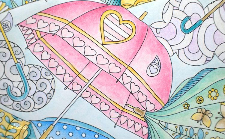 ハート柄の傘を水彩色鉛筆でピンクに塗っている
