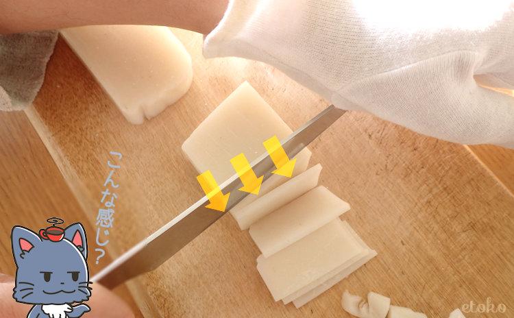 切り餅に包丁をあてて左手で押さえている