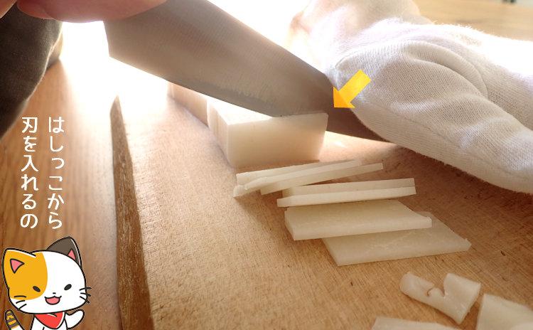 切り餅の端から包丁の刃をあてて切りこんでいる