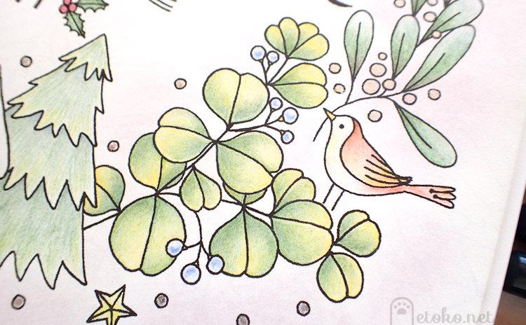 葉をくわえた小鳥と植物をダーウェントアーチストで塗っている