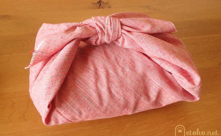 熱々の湯たんぽをタオルをはさんで付属袋に入れた上から風呂敷で包んでいる